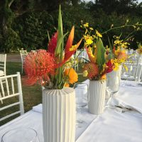 Tropical floral centerpieces for a rehearsal dinner set up for a Big Island destination wedding by Destination wedding planner, Mango Muse Events