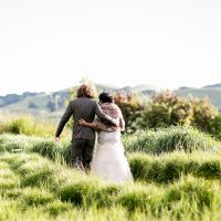 Bride and groom walking in a field at their Sonoma wedding by Destination wedding planner, Mango Muse Events