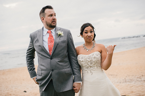 Bride and groom making faces on the beach at their Hawaii destination wedding by Destination wedding planner, Mango Muse Events