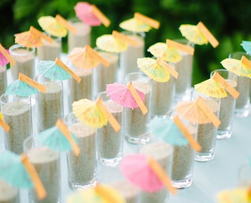 Cocktail umbrella seating escort cards in sand for a Hawaii destination wedding by destination wedding planner, Mango Muse Events