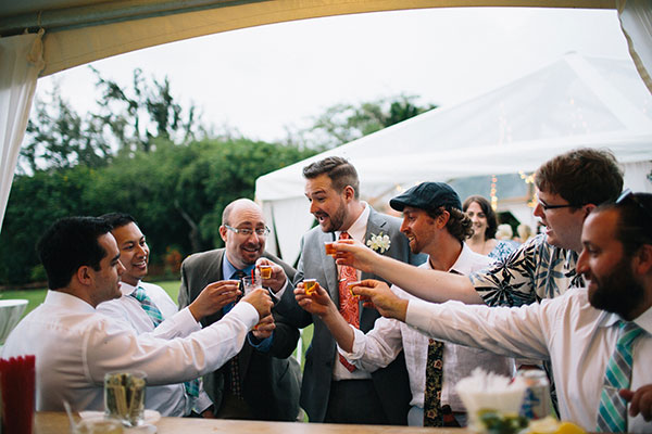 Groom and guests toasting at the wedding bar at a Hawaii destination wedding by destination wedding planner, Mango Muse Events