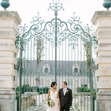 Bride and groom at the gate of the France chateau for their wedding by Destination wedding planner Mango Muse Events