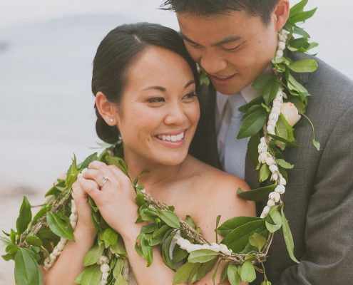 ride and groom with a Hawaiian maile pikake lei at their Hawaii wedding by Destination wedding planner, Mango Muse Events