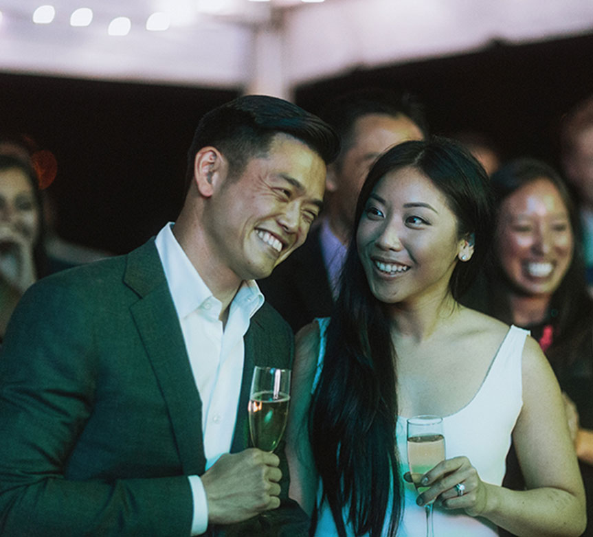 Bride and groom smiling during toasts at their Vancouver wedding by Destination wedding planner, Mango Muse Events