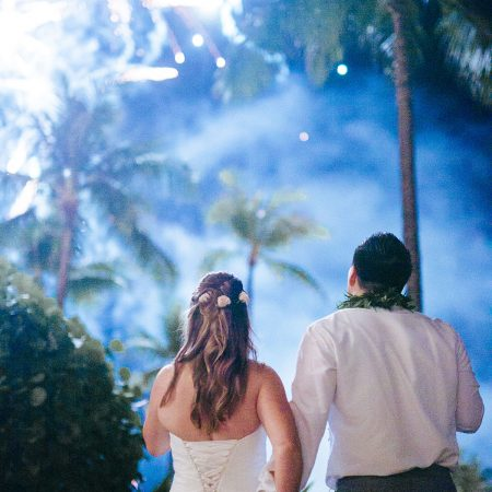 Bride and groom enjoying fireworks at a Hawaii destination wedding by Destination wedding planner Mango Muse Events