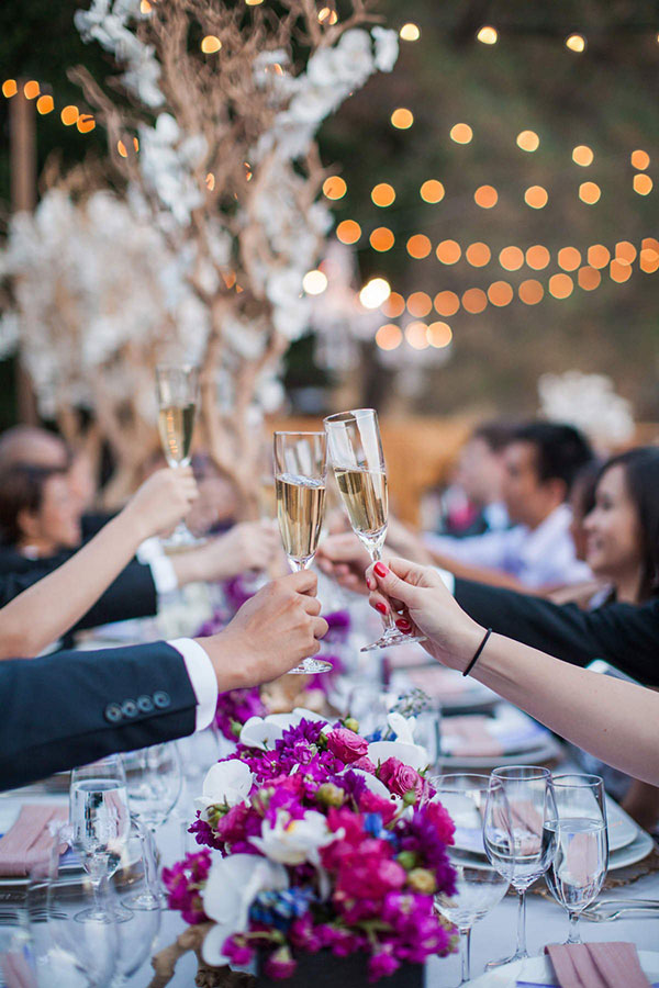 Wedding guests toasting with champagne at a destination wedding in wine country at Calistoga Ranch by destination wedding planner Mango Muse Events