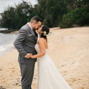 Bride and groom kissing at their beach wedding in Hawaii by destination wedding planner Mango Muse Events