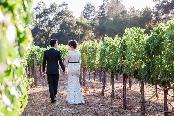 Bride and groom walking in a vineyard at their Calistoga destination wedding by Destination wedding planner Mango Muse Events