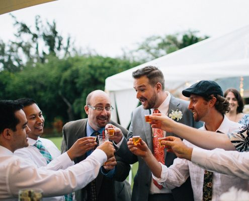 Groom and guests toasting at the wedding bar at a Hawaii destination wedding by Destination wedding planner Mango Muse Events