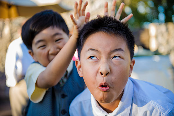 Kids playing and making faces at a wedding in Sonoma by Destination wedding planner, Mango Muse Events