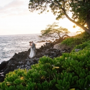 Bride and groom kissing at sunset on the rocks at a Big Island destination wedding in Hawaii by Destination wedding planner Mango Muse Events