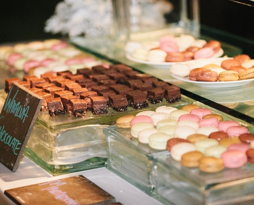 Dessert bar with chocolate bars and macarons at a destination wedding in Hawaii at Lanikuhonua by Destination wedding planner Mango Muse Events
