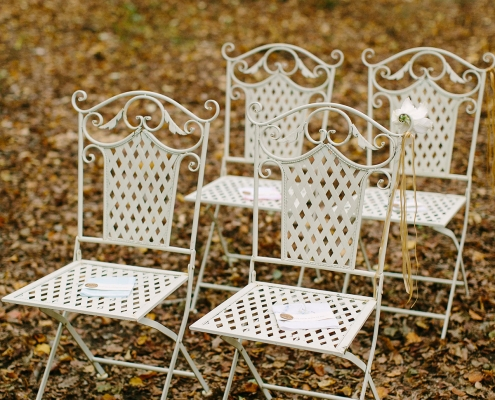 White ceremony chairs set up with vintage handkerchiefs for a forest wedding at a French Chateau in Loire Valley France by Destination wedding planner Mango Muse Events