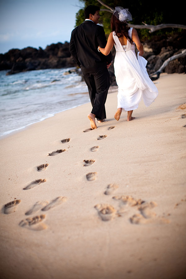 Bride and groom walking on the beach at their Maui wedding by Destination wedding planner Mango Muse Events