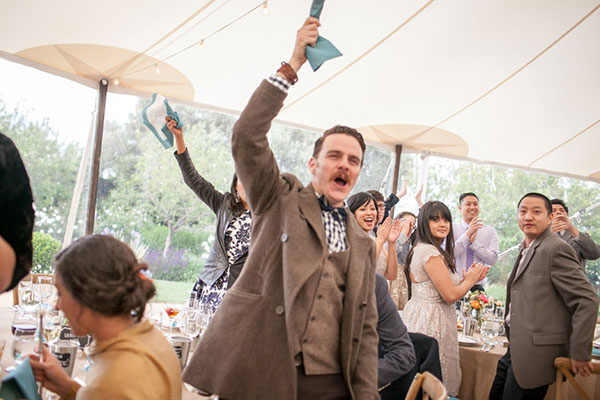 Wedding guests cheering at a destination wedding at Cornerstone Sonoma by Destination wedding planner Mango Muse Events