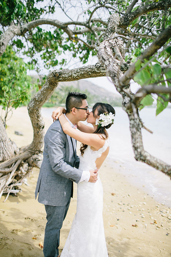 Bride and groom kissing on the beach at their Hawaii wedding by Destination wedding planner Mango Muse Events