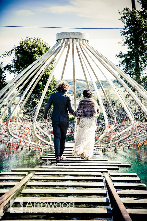 Bride and groom walking to an art installation sculpture at their Cornerstone Sonoma wedding by Destination wedding planner Mango Muse Events