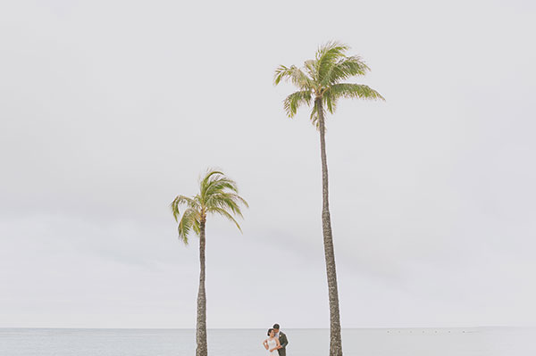 Couple with palm trees at a beach wedding in hawaii by Destination wedding planner Mango Muse Events