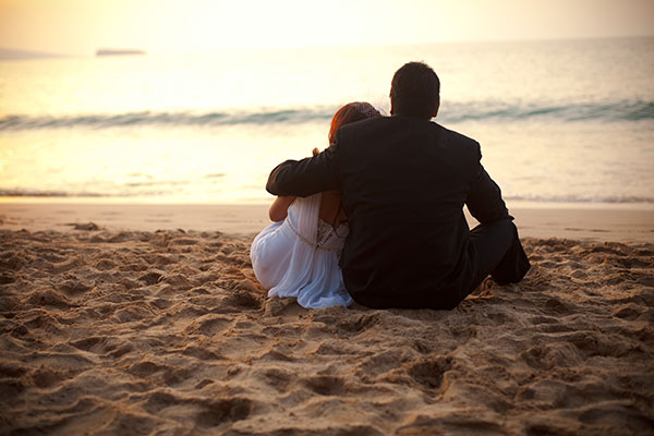 Newlywed couple on the beach enjoying the sunset at their wedding in Maui by destination wedding planner Mango Muse Events