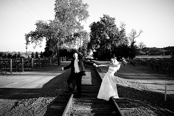 Bride and groom having fun on some old train tracks at their wine country wedding by Destination wedding planner Mango Muse Events