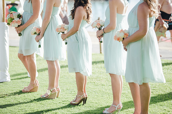 Bridesmaids in aqua dresses and peach and white bouquets at a wedding ceremony in Hawaii by destination wedding planner Mango Muse Events