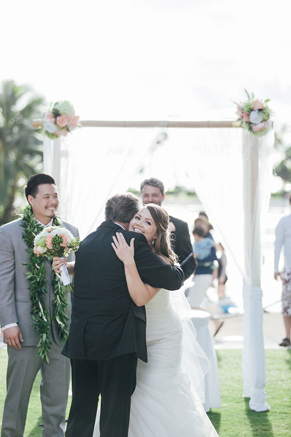 Bride and her father hugging at a destination wedding in Hawaii by Destination wedding planner Mango Muse Events