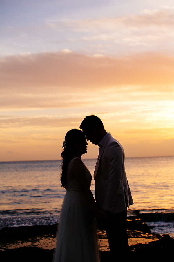 Sunset beach wedding in Hawaii by Destination wedding planner Mango Muse Events
