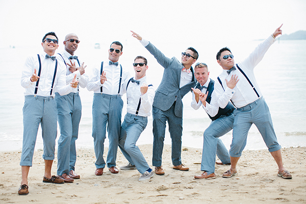 Groom and groomsmen having a good time at a beach wedding in Hawaii by Destination wedding planner Mango Muse Events