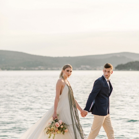 Bride and groom strolling along the Adriatic sea at a Croatia destination wedding by destination wedding planner Mango Muse Events