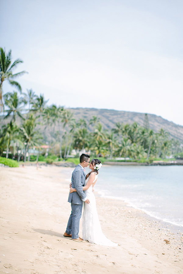 Bride and groom enjoy a moment and kiss at their Hawaii beach wedding by destination wedding planner Mango Muse Events