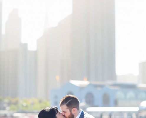 Bride and groom wedding kiss at the Ferry Building in San Francisco for a destination wedding by destination wedding planner Mango Muse Events