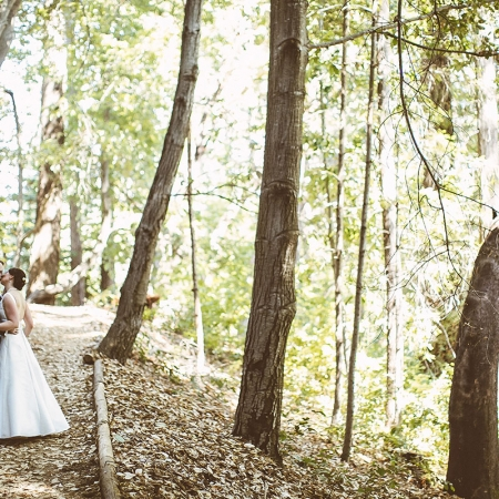 Bride and groom sharing a kiss in the woods at their Ben Lomond woodland wedding by destination wedding planner Mango Muse Events
