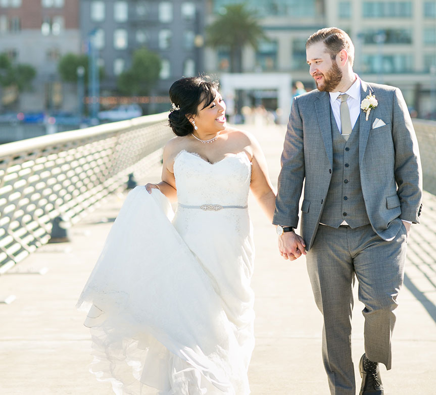 Happy couple taking a stroll at the Ferry Building at their San Francisco destination wedding by destination wedding planner Mango Muse Events