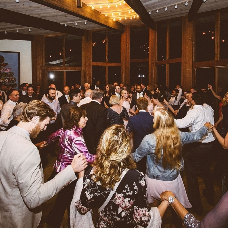 Guests participating in a lively hora dance at a woodland wedding by destination wedding planner Mango Muse Events