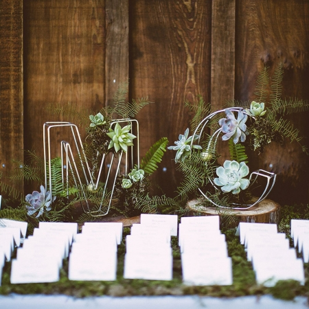 Bride and groom initials decorated with succulents and ferns with escort cards on a bed of moss for a woodland wedding by destination wedding planner Mango Muse Events