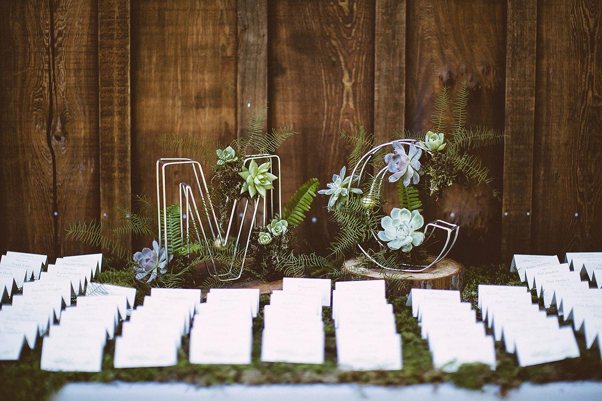 Initials Succulent Arrangement Escort Card Display Woodland Wedding Marissa Connor Destination Wedding Planner Mango Muse Events Mango Muse Events