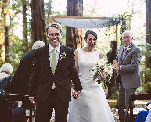 Just married happy couple walking down the aisle at their Ben Lomond woodland wedding by destination wedding planner Mango Muse Events
