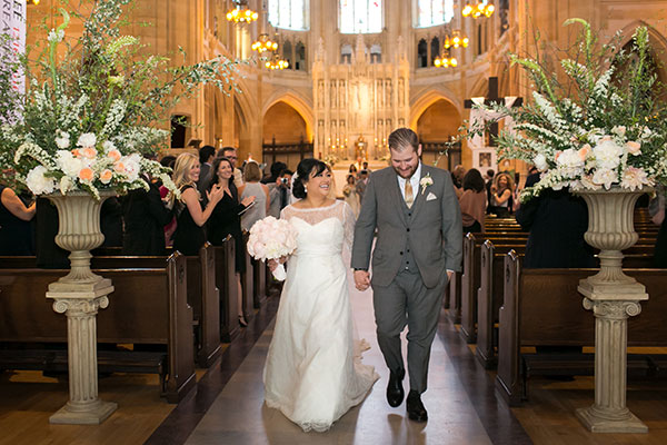 Newlyweds walking down the aisle at a St. Dominic's Catholic church wedding ceremony in San Francisco by destination wedding planner Mango Muse Events