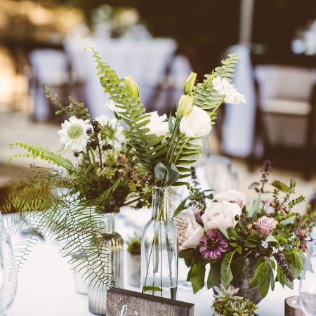 Rustic woodland wedding centerpieces with locally grown flowers and ferns at a woodland wedding by destination wedding planner Mango Muse Events