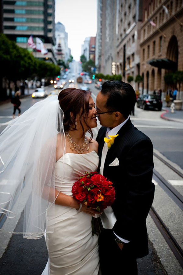 Bride and groom sharing a wedding kiss on the streets of San Francisco by Destination wedding planner Mango Muse Events