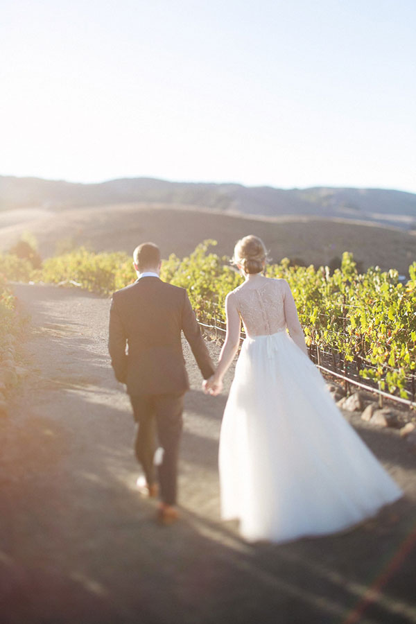 Bride and groom walking in the vineyards at their Sonoma wine country destination wedding by Destination wedding planner Mango Muse Events