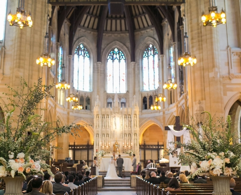 Iconic San Francisco wedding ceremony at St. Dominic's Catholic Church with asymmetrical garden arrangements by destination wedding planner Mango Muse Events