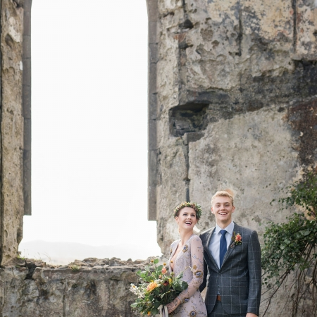 Bride and groom at their wedding ceremony amongst beautiful ruins on the Isle of Skye for a Scotland destination wedding by destination wedding planner Mango Muse Events