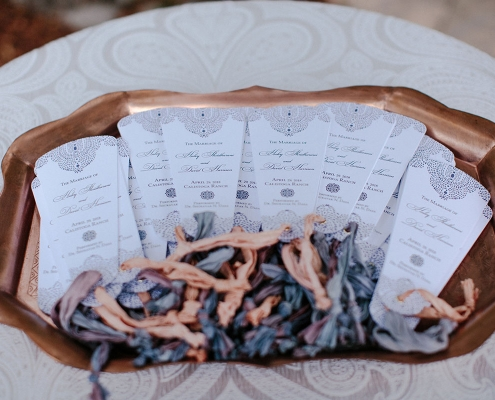 Intricately designed wedding ceremony programs with recycled sari ribbon for a multicultural wedding by destination wedding planner Mango Muse Events