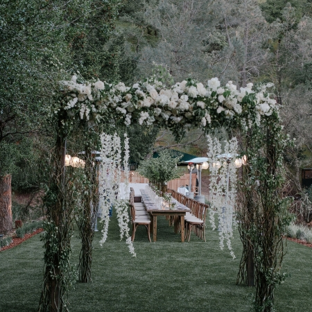 Modern mandap reused for a grand entrance to the wedding reception on the lawn at Calistoga Ranch by destination wedding planner Mango Muse Events