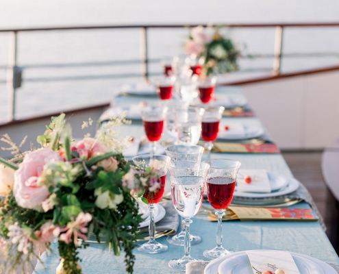 Rich blue and red wedding tablescape on yacht for a Croatia wedding reception by destination wedding planner Mango Muse Events