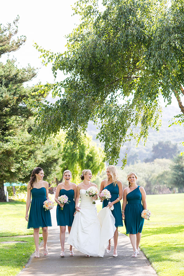 Bride and her bridesmaids in teal dresses enjoying a moment at a wedding in Carmel at the Quail Lodge by destination wedding planner Mango Muse Events