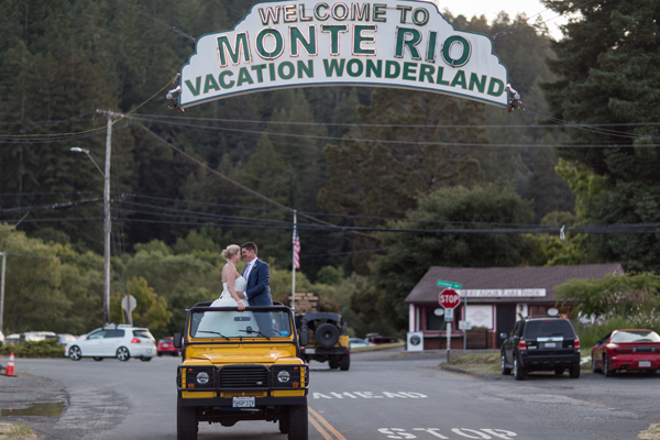 Couple in their jeep with the Monte Rio vintage sign at their russian river wedding by destination wedding planner Mango Muse Events