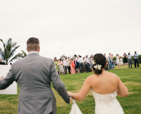 Wedding guests excitedly greeting the bride and groom at a Hawaii destination wedding by destination wedding planner Mango Muse Events