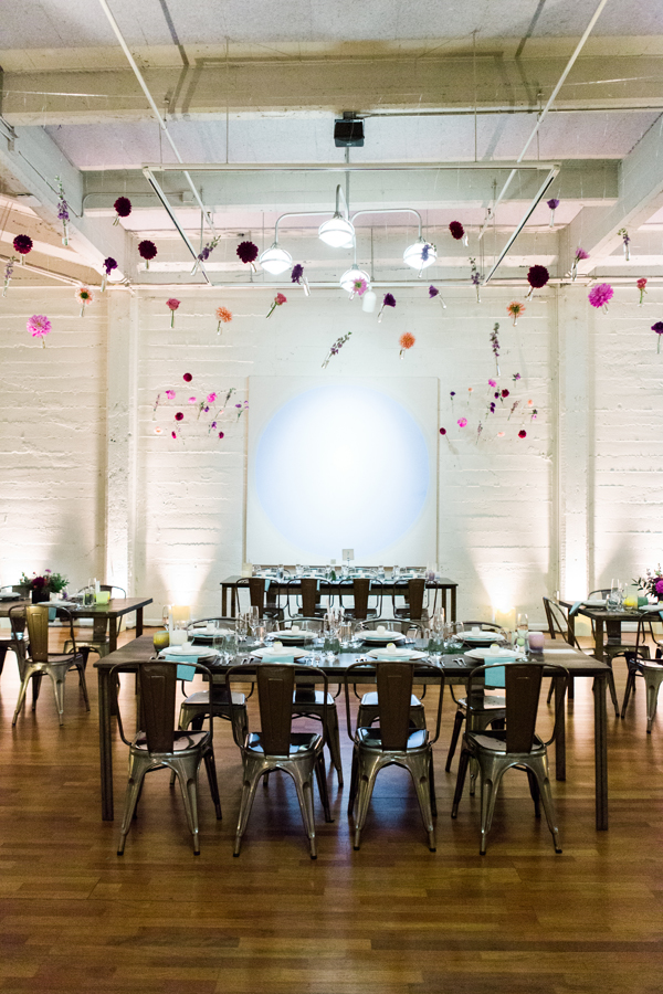 Hanging flower test tubes at a science art gallery wedding reception at Terra gallery in San Francisco by destination wedding planner Mango Muse Events